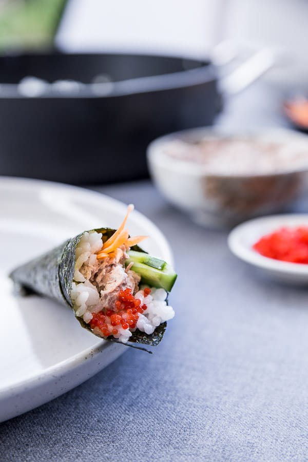 One sushi roll stuffed with tuna, carrot and cucumber on a plate with ingredient bowls in the background.