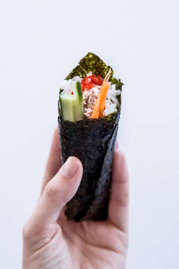 One temaki sushi roll held by hand.