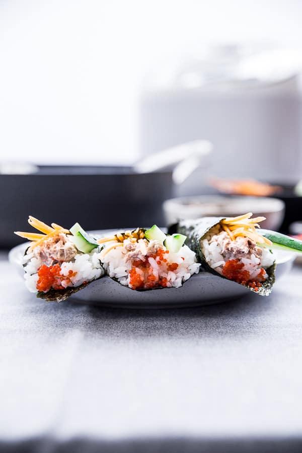 Three temaki sushi on a plate.