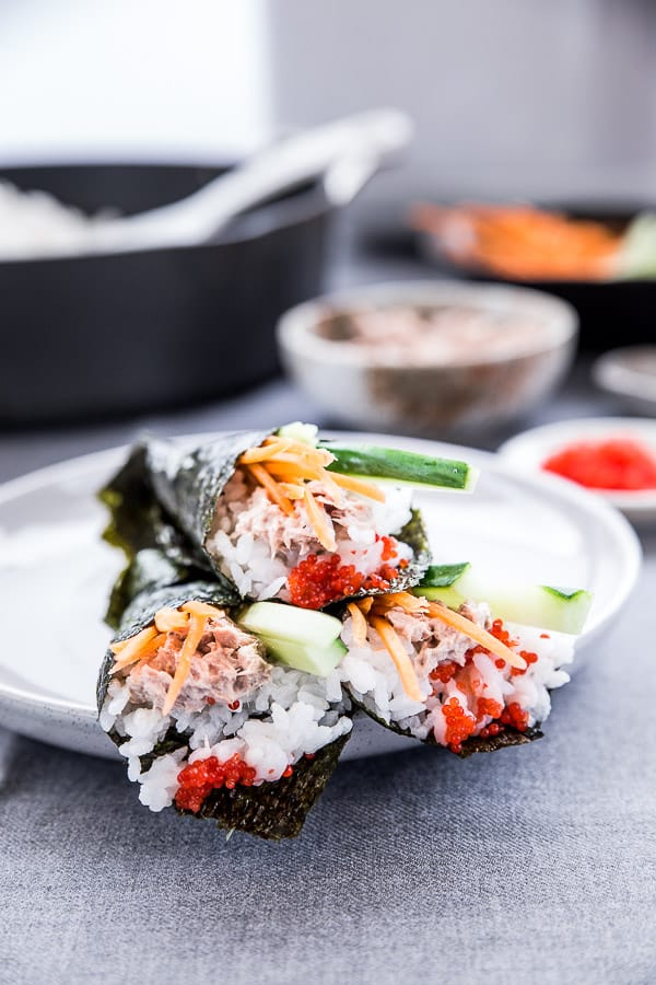A close up of three handmade sushi rolls on a plate.