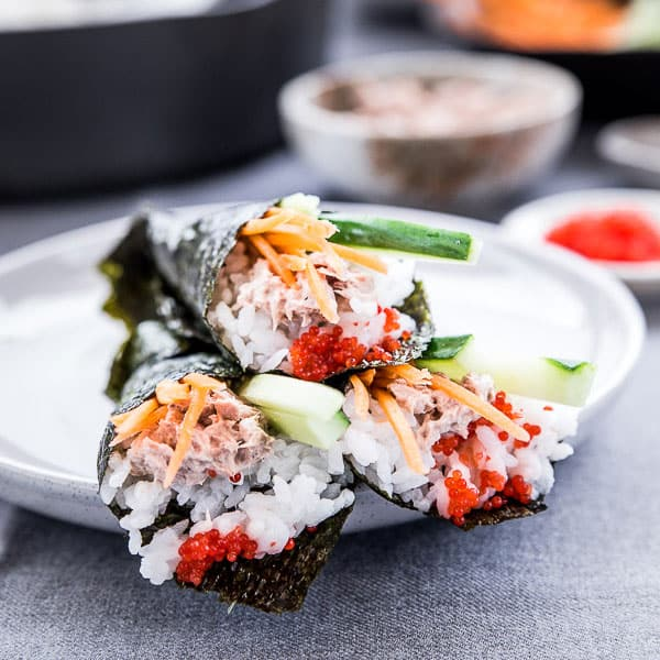 Three rolled sushi cones on a plate.