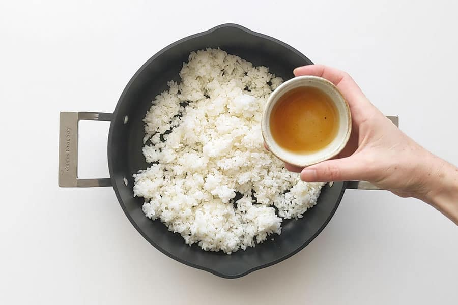 Mixing sushi vinegar into rice.