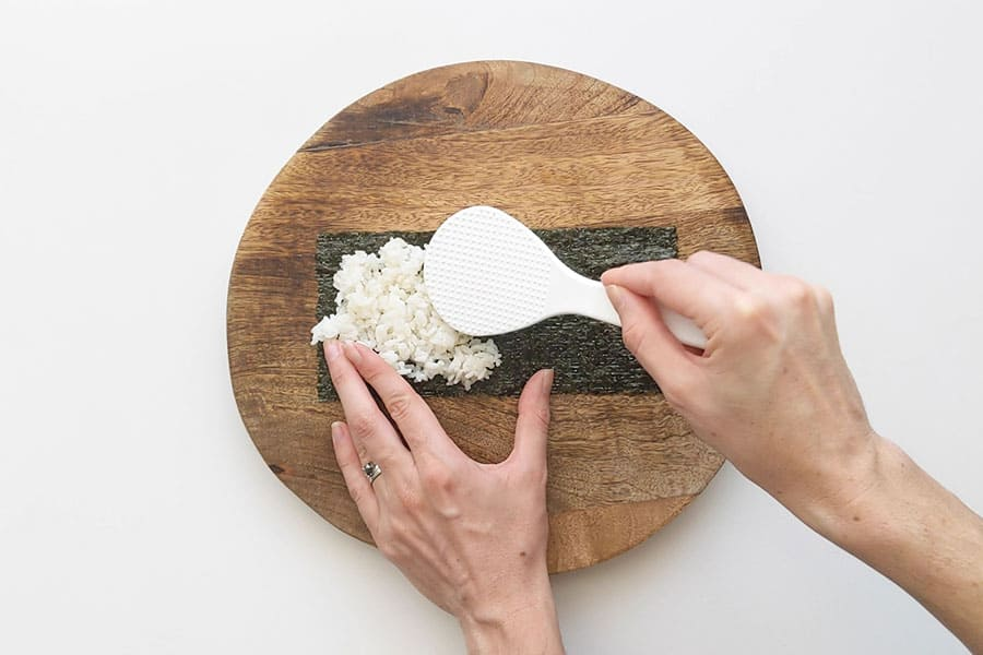 Layering rice onto nori sheets.