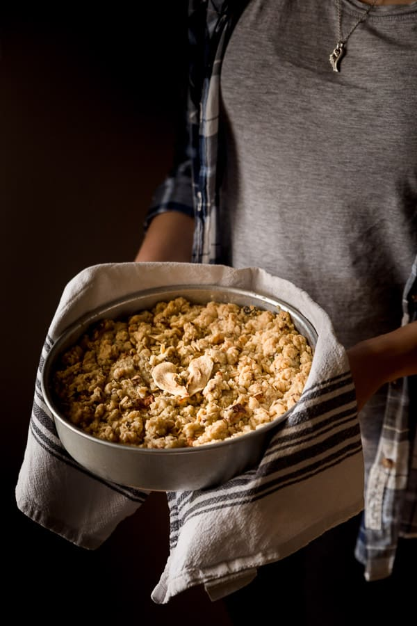A person holding a freshly baked apple crumble in a baking dish.