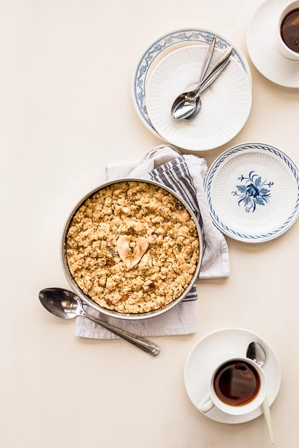 Freshly baked English crumble on a table surrounded by plates and spoons.