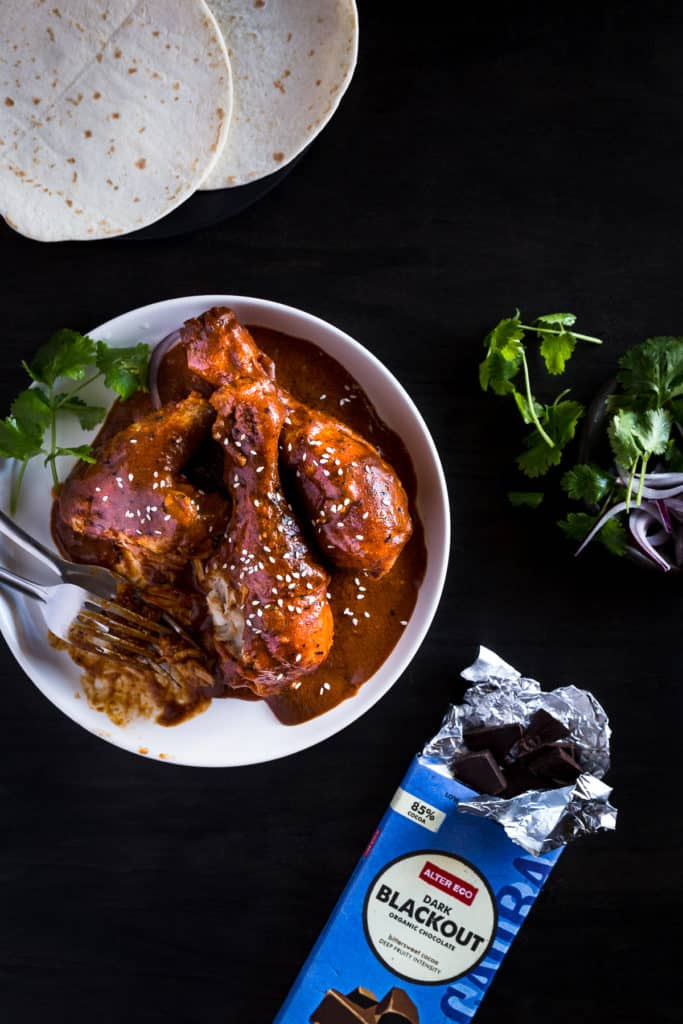 A plate of Mexican chocolate chicken next to a packet of dark chocolate and pile or tortillas.