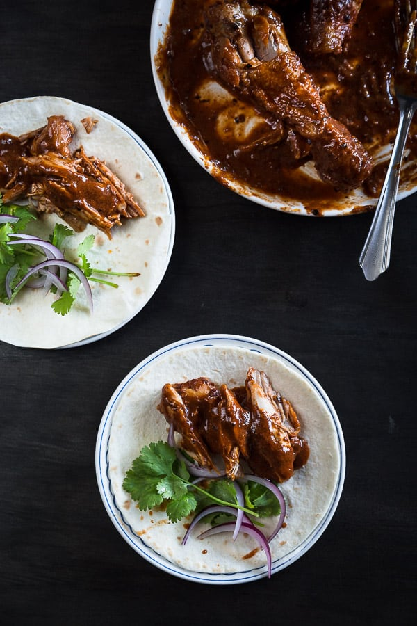 Shredded chicken in chocolate mole sauce on tortillas.