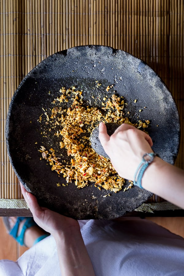 Grinding the spices for bumbu bali in a traditional Indonesian mortar & pestle.