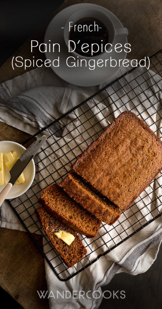 Slices of french spice bread on a cooling tray next to a dish of butter.