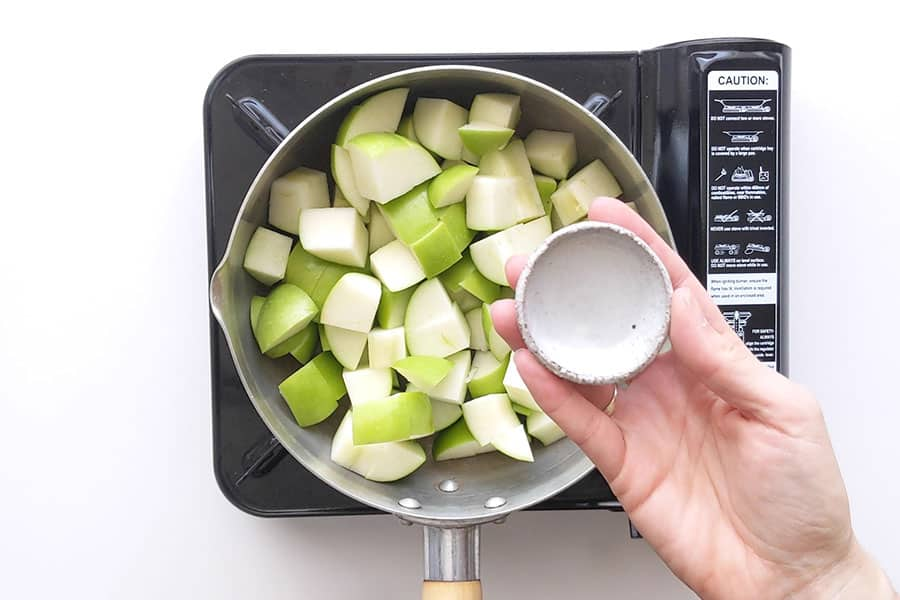 Saucepan with chopped green apples ready to cook.