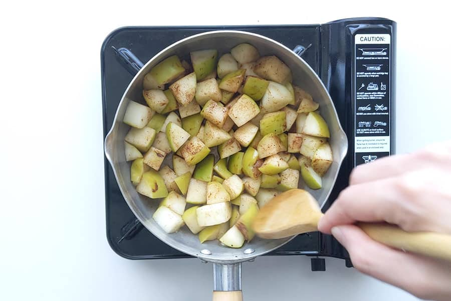 Mashing apples into applesauce with a wooden spoon.