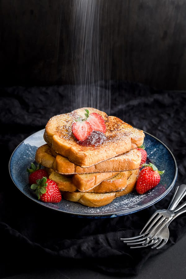Sprinkling icing sugar over a stack of brioche french toast and strawberries.