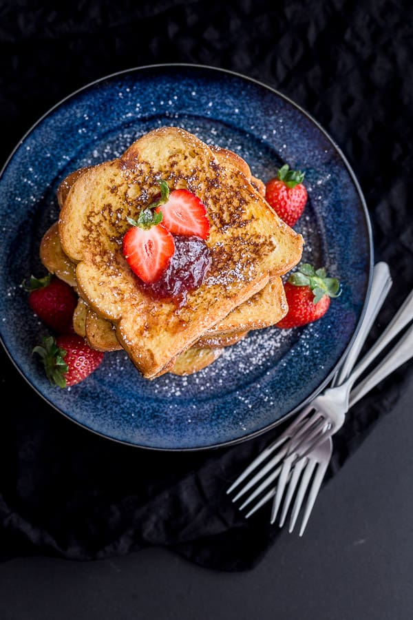 A stack of Korean style french toast covered with strawberry jam, fresh strawberries and a sprinkling of icing sugar.