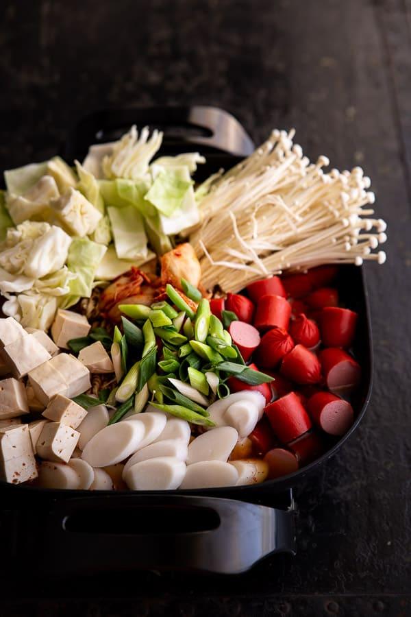 Korean army stew ingredients simmering in an electric frypan.
