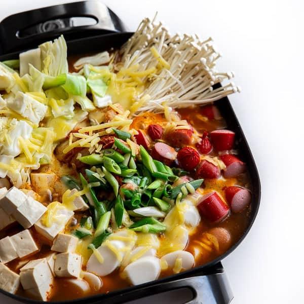 Stew ingredients simmering in the spicy Korean stew broth.