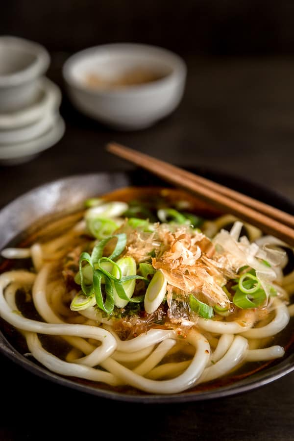 Udon noodle soup in a bowl garnished with spring onion, katsuoboshi (bonito flakes) and Japanese chilli flakes.
