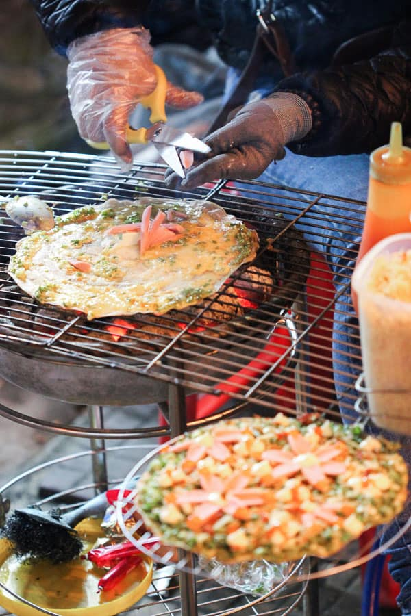 The Vietnamese street food version of grilled rice paper pizza, being cooked on the steps of the markets in Da Lat, Vietnam.