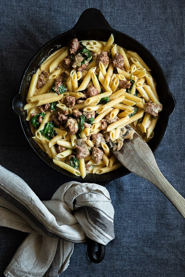 Creamy Italian Sausage Pasta in cast iron pan with wooden spatula.