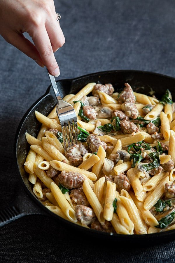 Creamy Italian sausage pasta in cast iron pan with hand picking up sausage with fork.