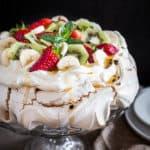 Australian Pavlova Dessert Meringue on cake stand with side plates.