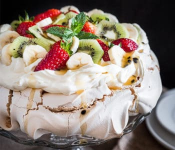 Australian Pavlova Dessert Meringue on cake stand with side plates.