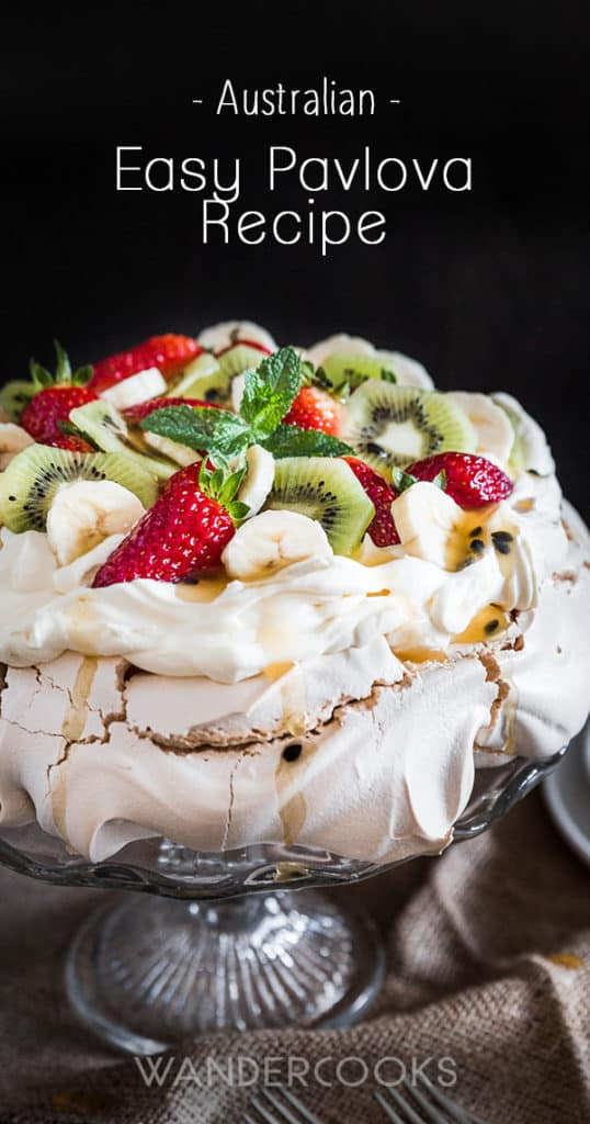 Australian Pavlova Dessert Meringue on cake stand with forks and side plates.