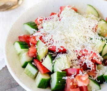 Shopska salad in a bowl covered in grated cheese.