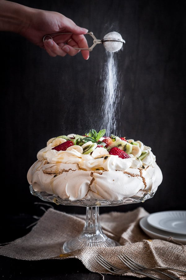 Australian Pavlova Dessert Meringue on cake stand with hand sprinkling icing sugar over the top.