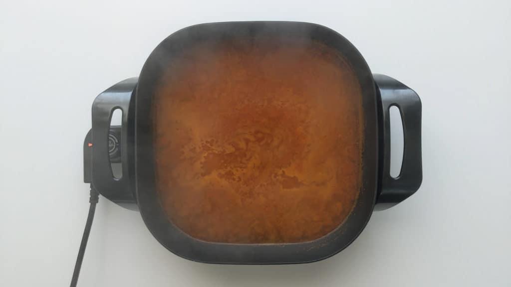 Tteokbokki soup stock in a fry pan.