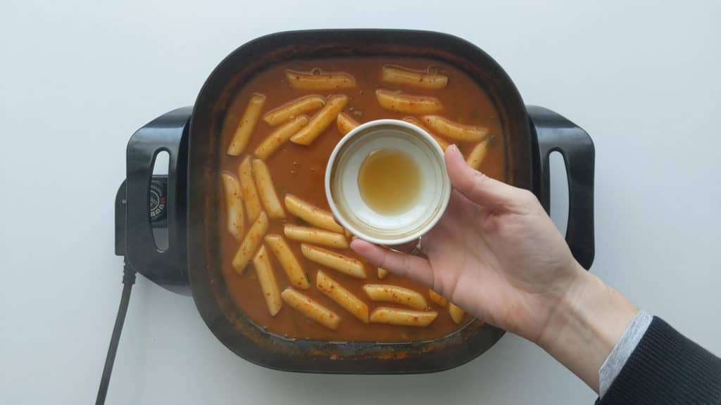 Sesame oil being added to the cooked tteokbokki just before serving.