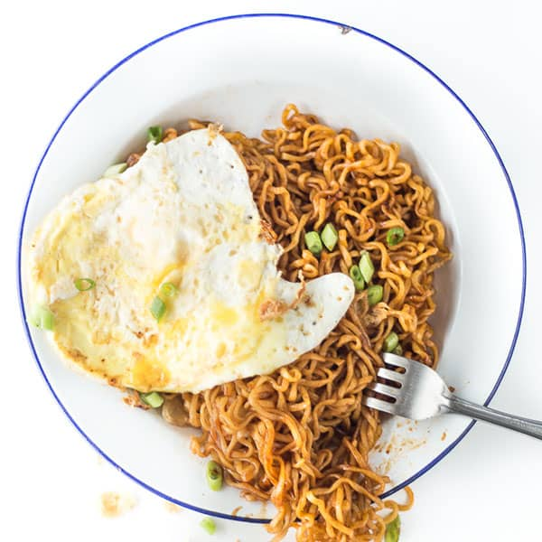 Mee goreng on a plate covered in fried egg.