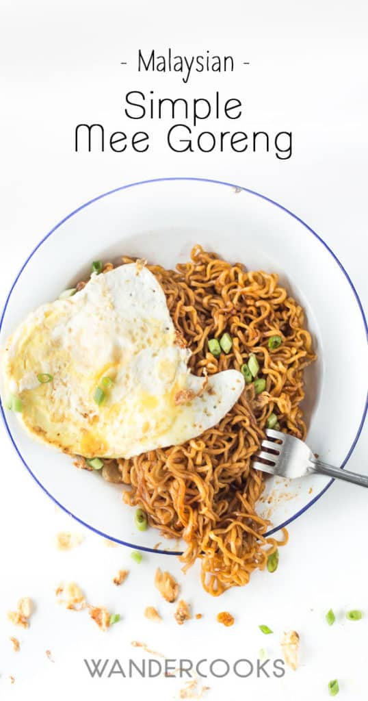 Mee goreng on a plate covered in a fried egg.