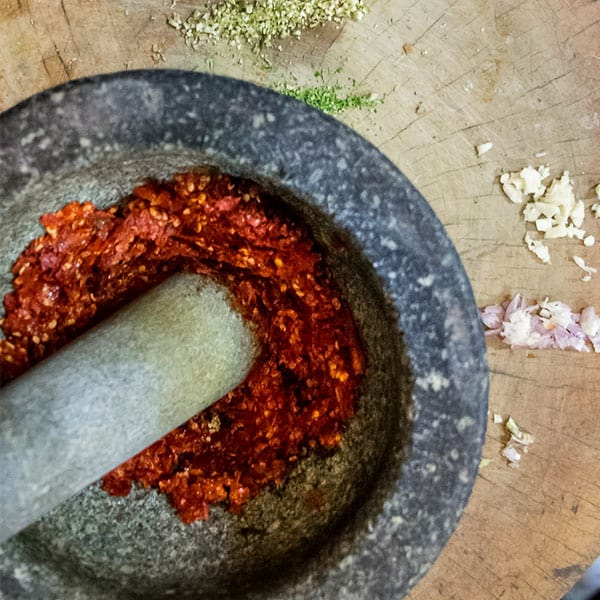 Crushed chillis in a mortar and pestle, with other panang curry paste ingredients on a wooden board.