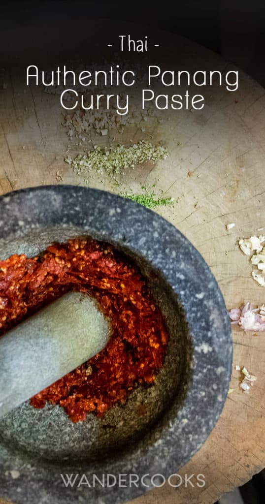 Dried red chillis in a mortar and pestle surrounded by other panang curry ingredients on a wooden chopping board.