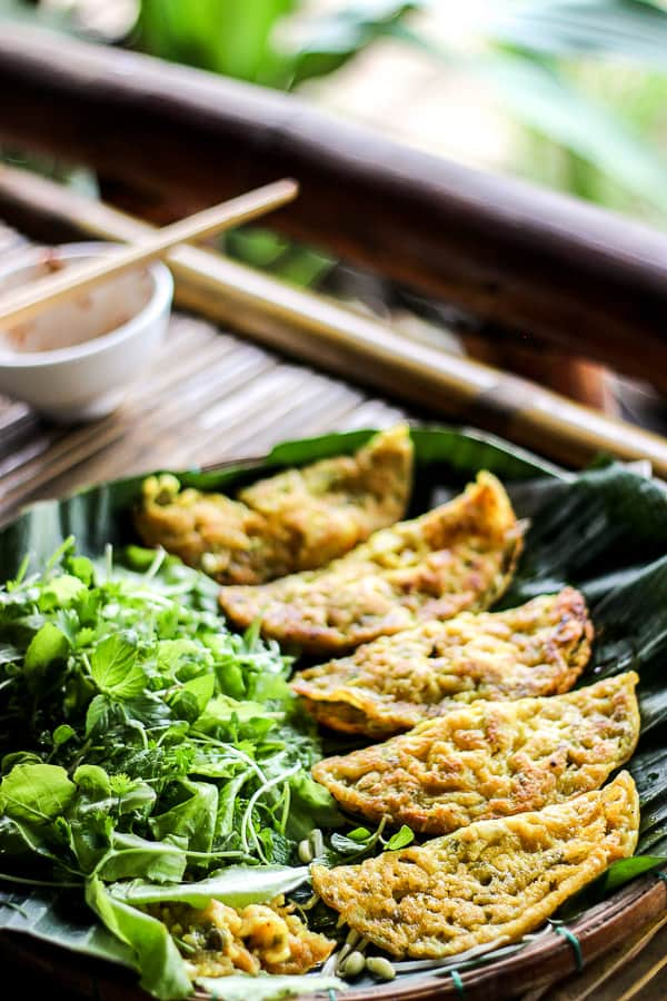 Banh Xeo on weaved plate with banana leaves.
