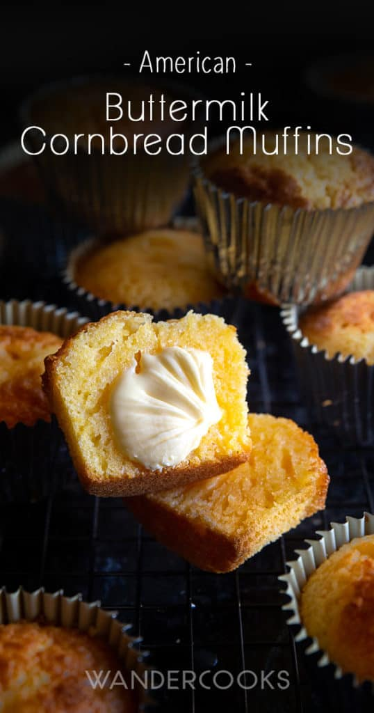 Cornbread muffin cut in half with butter and surrounded by muffins in patty pans.