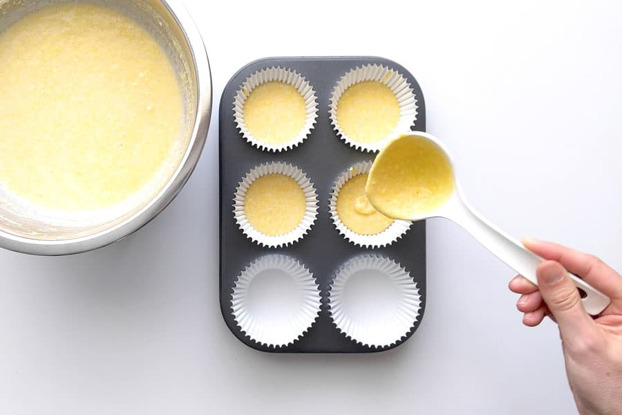 Ladling cornbread mixture into patty pans.