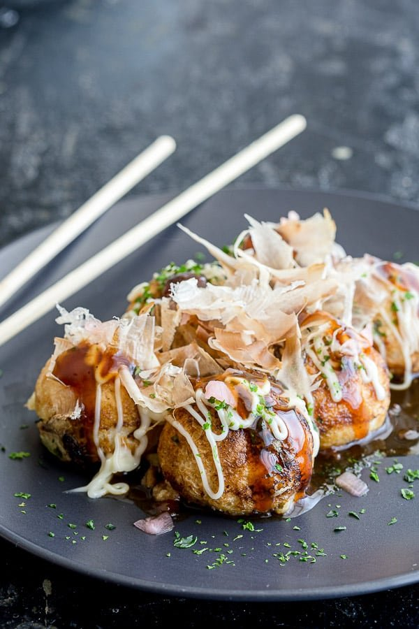 Plate of takoyaki balls topped with homemade takoyaki sauce, kewpie mayonnaise, aonori and katsuoboshi.