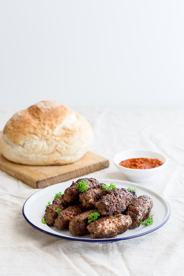Plate of cevapi, Bosnian homemade sausages with lapinja bread and ajvar spread.