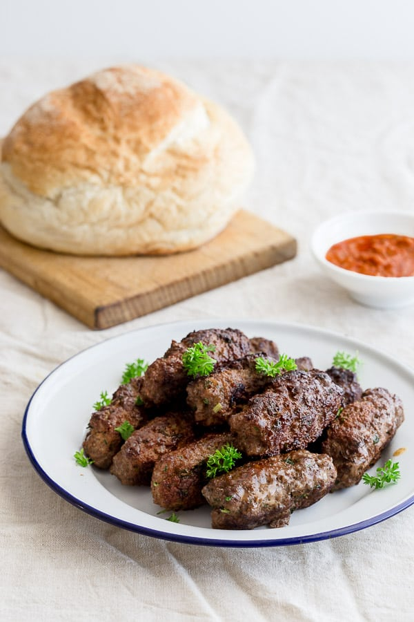 Plate of Balkan beef sausages with lapinja bread and ajvar spread.