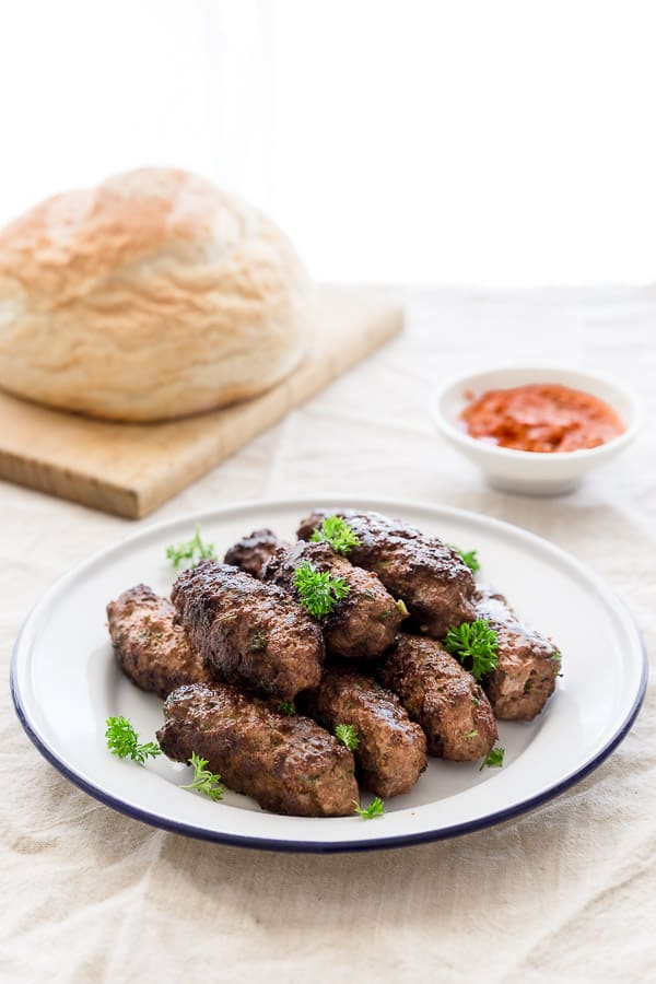 Plate of Bosnian homemade sausages with lapinja bread and ajvar spread.