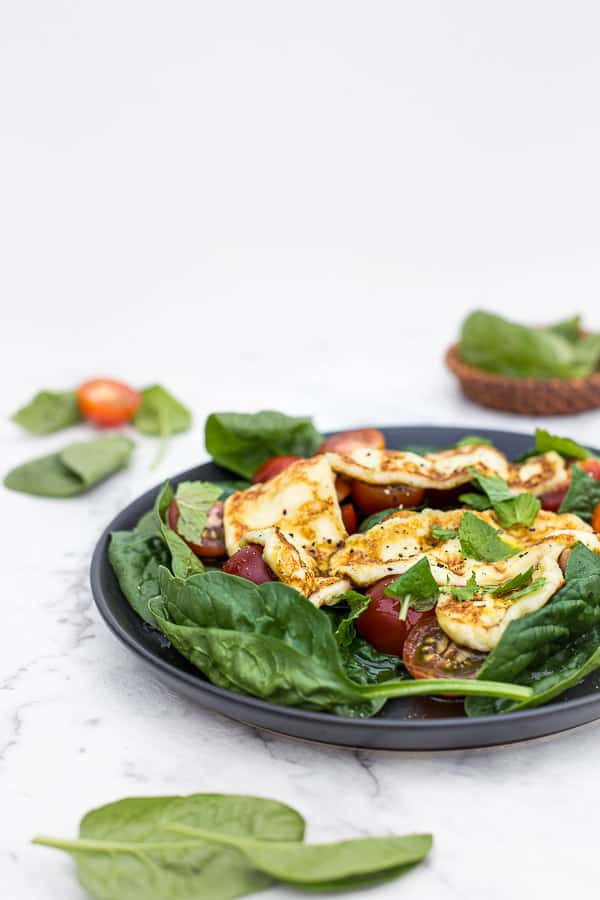 Haloumi salad on a dark plate with spinach leaves in background.