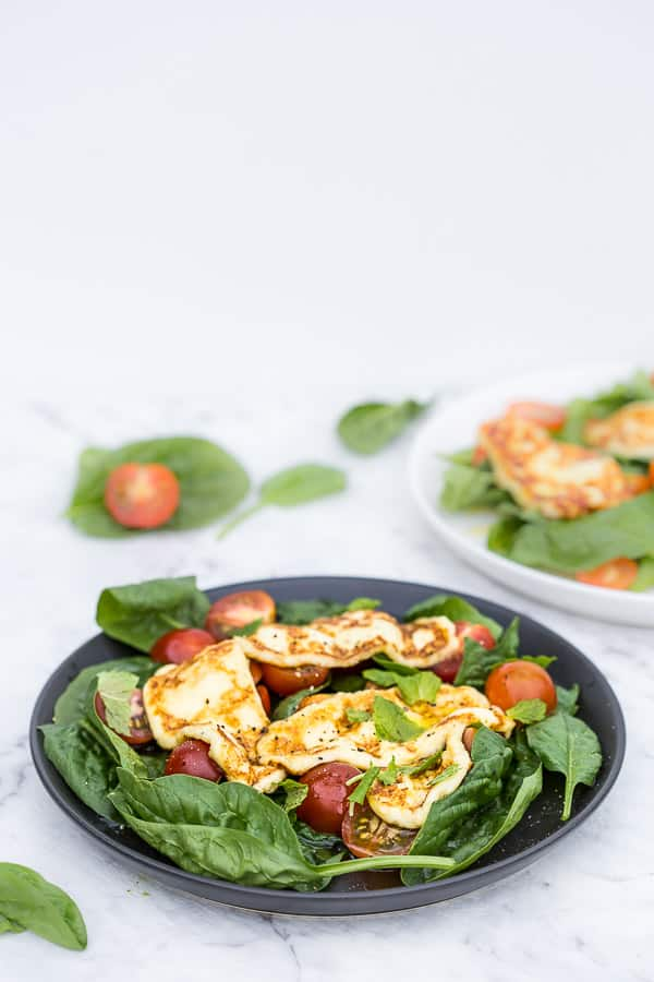 Plate of salad with haloumi, spinach leaves, tomatoes and mint.