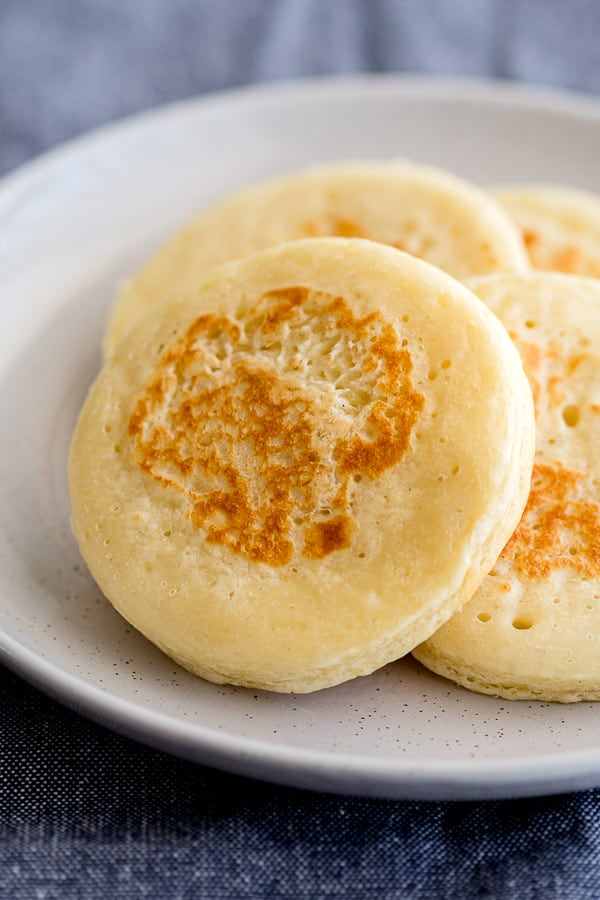 Fresh crumpets, lightly browned on a plate.