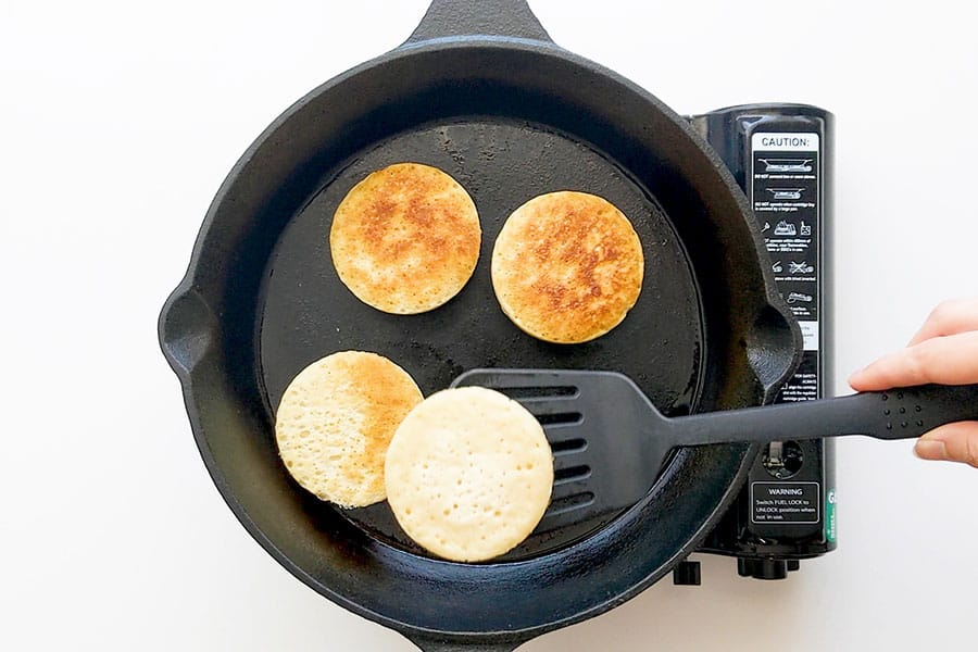Flipping crumpets on a frying pan.