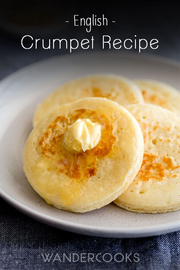 Golden crumpets with butter and honey on a plate.