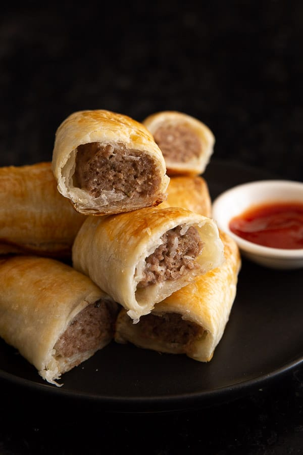 A stack of sausage rolls with a dish of tomato sauce, perfect for dipping!