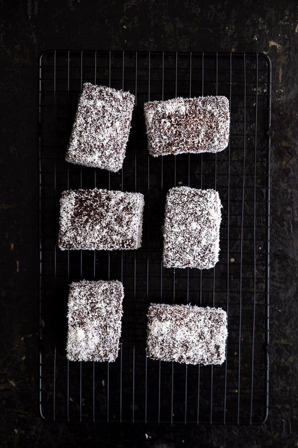 Six lamingtons sitting on a wire rack with a dark background.
