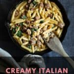 Creamy Italian sausage pasta in cast iron pan.