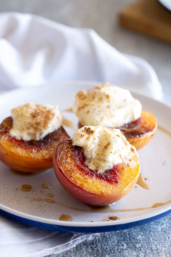 White plate with three caramelized peaches, topped with sour cream.